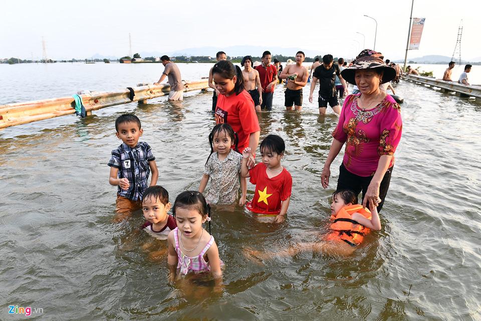 Bà Nguyễn Thị Hồng cho biết cảnh này diễn ra thường xuyên mỗi khi đường bị ngập. Hôm nay tranh thủ chiều chủ nhật, bà cho các cháu ra nghịch nước.