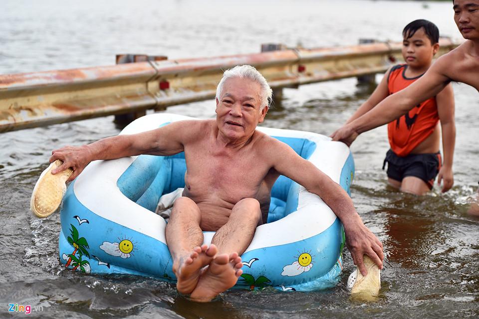 Ông Hà Danh Bình (71 tuổi) cho biết có thể bơi xa nhưng hôm nay được dịp vùng vẫy nhiều giờ nên mệt, nhờ con cháu mang phao ra nằm lênh đênh trên nước.