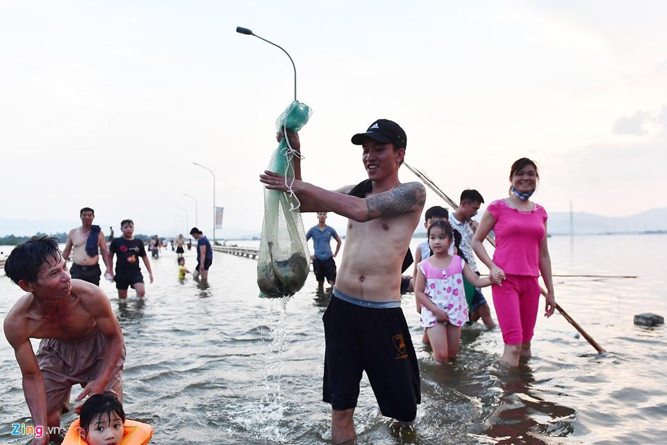Khang Duy, một thanh niên sống ở thị trấn Quốc Oai cho biết sẽ mang những chú cá này về làm thịt ăn tối và chia cho người thân, bạn bè.